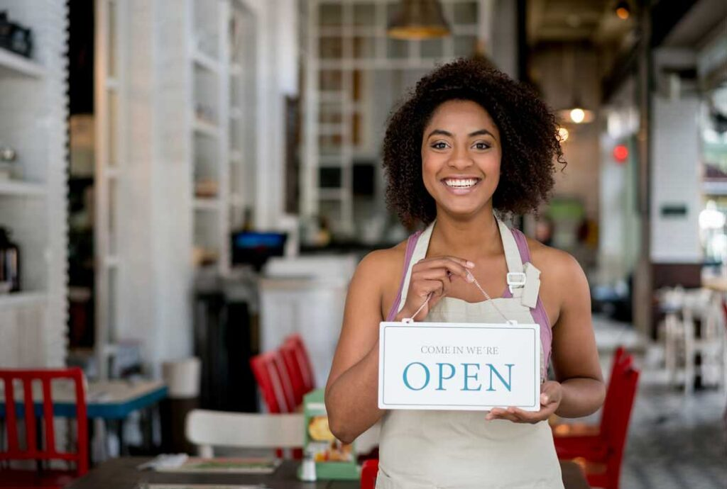 Happy African American waitress holding an open sign at a restaurant and looking at the camera smiling