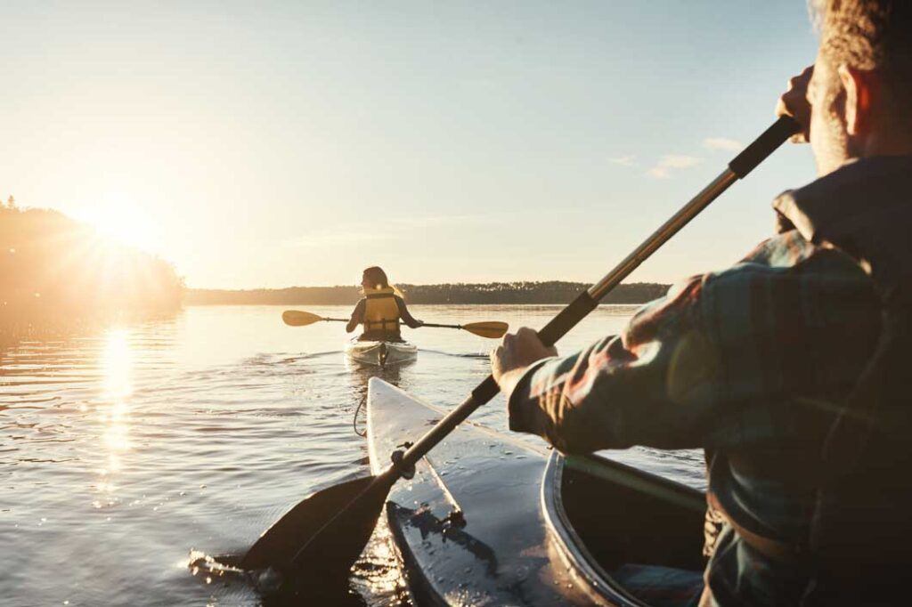 Shot of a young couple kayaking on a lake outdoors
